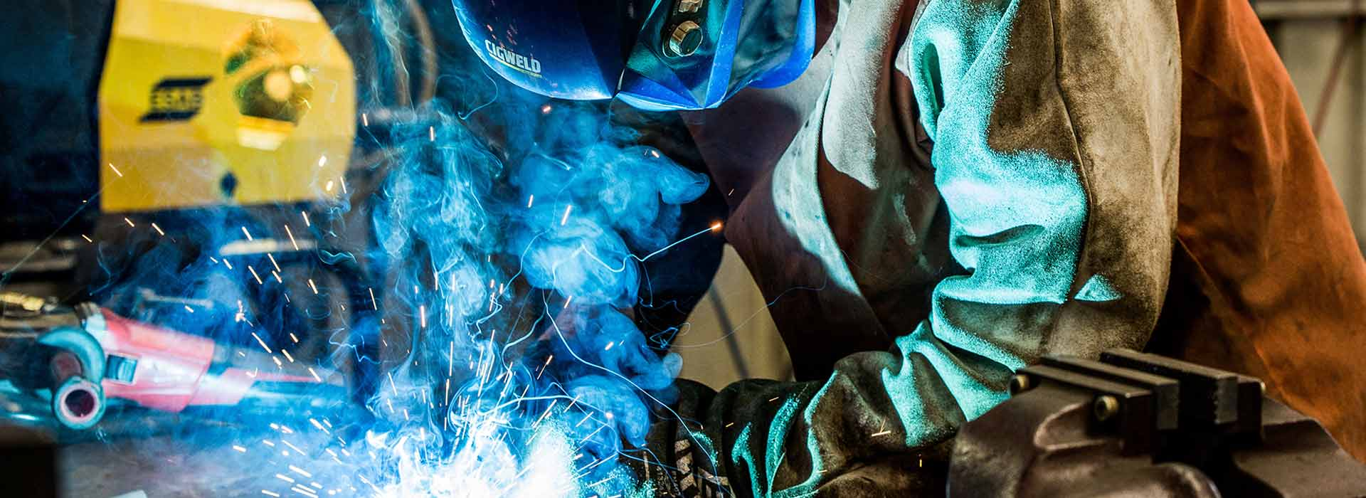 Person doing welding work, illuminated by sparks and smoke, wearing protective face shield, leather jacket and gloves