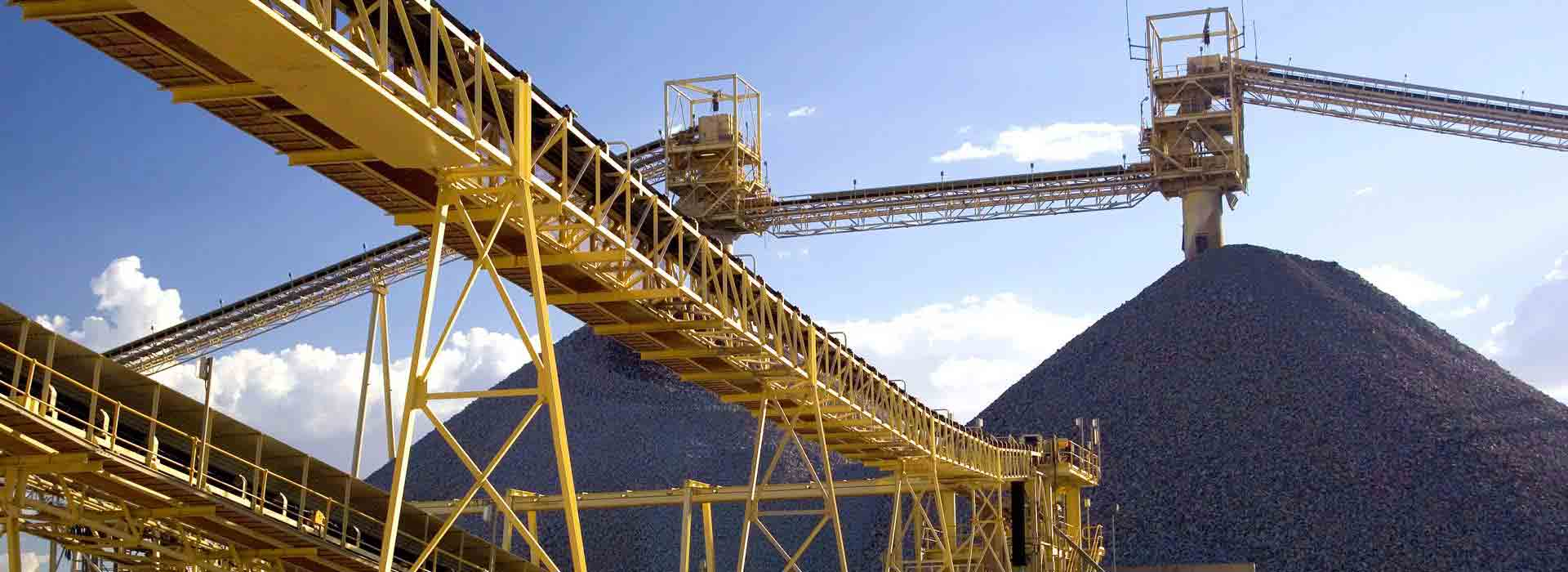 Yellow metal conveyor belt structures in the open air, with two large piles of gravel piled up behind the metal structures